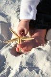 Niño que sostiene una estrella de mar en la playa imagen de archivo