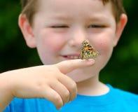 Niño que sostiene una mariposa Fotos de archivo