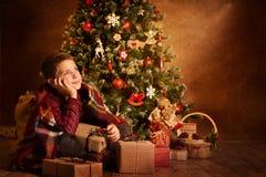 Niño que sueña debajo de árbol de Navidad, niño de la Navidad del muchacho de la Feliz Año Nuevo imágenes de archivo libres de regalías