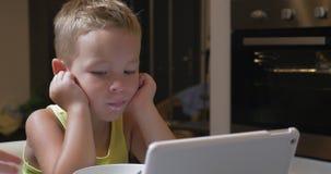 Niño que tiene comida con las historietas en el cojín almacen de video