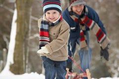 Niño que tira del trineo con paisaje del invierno Foto de archivo