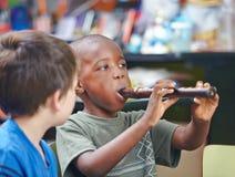 Niño que toca la flauta en escuela de música Fotos de archivo