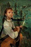 Niño que toca la guitarra contra la pared arruinada grunge Imagenes de archivo