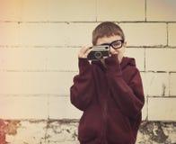 Niño que toma la fotografía con la cámara del vintage Fotos de archivo