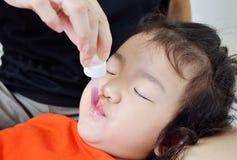 Niño que toma la medicina con el dropper fotos de archivo