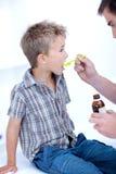 Niño que toma la medicina de la tos Fotos de archivo