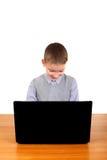 Niño que trabaja en el ordenador portátil Imagen de archivo