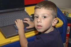 Niño que usa el ordenador foto de archivo