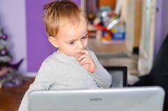 Niño que usa el ordenador portátil en casa Foto de archivo libre de regalías