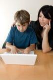 Niño que usa la computadora portátil mientras que el adulto supervisa Fotos de archivo