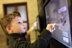 Niño que usa la pantalla táctil Fotos de archivo