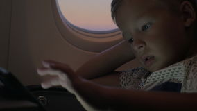 Niño que usa la tableta en aeroplano metrajes