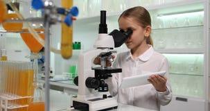 Niño que usa la tableta, microscopio en el laboratorio de química de la escuela, ciencia de trabajo 4K de la muchacha metrajes