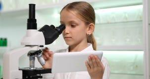 Niño que usa la tableta, microscopio en el laboratorio de química de la escuela, ciencia de trabajo 4K de la muchacha almacen de video