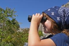 Niño que usa los prismáticos Imagenes de archivo