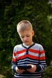 Niño que usa una tableta, retrato al aire libre Fotografía de archivo