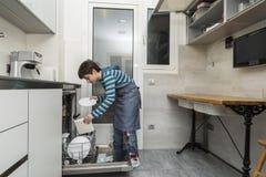 Niño que vacia el lavaplatos Imagen de archivo libre de regalías