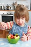 Niño quisquilloso que rechaza el pudín delicioso de la ensalada de fruta imagen de archivo libre de regalías