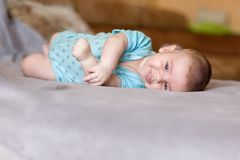 Niño recién nacido que miente en el sofá y la mirada linda foto de archivo libre de regalías