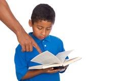 Niño rector del brazo en estudio de la biblia Imagen de archivo