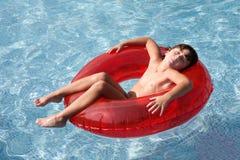 Niño Relaxed en la piscina Foto de archivo libre de regalías