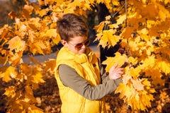 Niño rodeado por el follaje amarillo en otoño imagenes de archivo