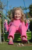 Niño rosado feliz de la muchacha en el oscilación