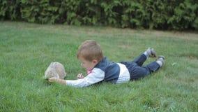 Niño rubio de la edad elemental feliz que miente en hierba en el parque con un pequeño conejito metrajes