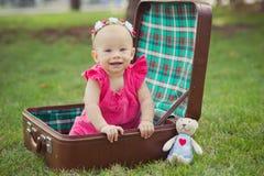 Niño rubio de la muchacha del bebé lindo que lleva el vestido rosado que se sienta en naturaleza verde del parque en tronco retro Fotos de archivo libres de regalías