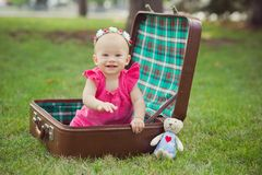 Niño rubio de la muchacha del bebé lindo que lleva el vestido rosado que se sienta en naturaleza verde del parque en tronco retro Foto de archivo