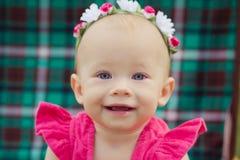 Niño rubio de la muchacha del bebé lindo que lleva el vestido rosado que se sienta en naturaleza verde del parque en tronco retro Fotografía de archivo libre de regalías