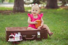 Niño rubio de la muchacha del bebé lindo que lleva el vestido rosado que se sienta en naturaleza verde del parque en tronco retro Imagen de archivo