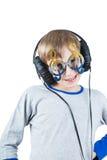 Niño rubio elegante hermoso que lleva los auriculares profesionales grandes y los vidrios divertidos Imágenes de archivo libres de regalías