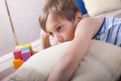 Niño rubio lindo que miente en un sofá que parece agujereado Fotografía de archivo