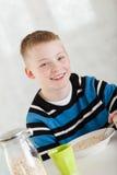 Niño rubio que ríe nerviosamente que come la harina de avena en cuenco Imagenes de archivo