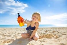 Niño sano sonriente en traje de baño en la costa que muestra la loción fotos de archivo libres de regalías