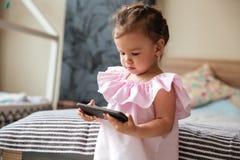 Niño serio de la niña dentro usando el teléfono móvil Imagen de archivo libre de regalías