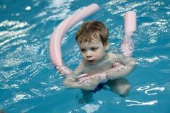 Niño serio que usa los tallarines de la piscina Imágenes de archivo libres de regalías