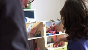 Niño sincero y papá que juegan con el tiro cerrado trasero SF de la casa de muñecas almacen de video