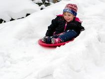 Niño sledding abajo de una colina Fotografía de archivo libre de regalías