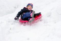 Niño sledding abajo de una colina en invierno Fotos de archivo libres de regalías