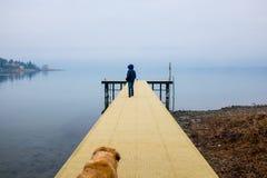 Niño sobre un embarcadero de madera en el lago Maggiore, niebla del invierno en el la Imagenes de archivo