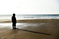 Niño solitario en una playa antes de la puesta del sol Foto de archivo libre de regalías