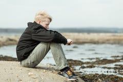 Niño solo con los brazos alrededor de rodillas afuera Fotografía de archivo