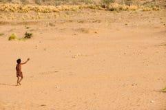Niño solo, funcionamiento en la arena/el polvo/la suciedad, la India foto de archivo libre de regalías