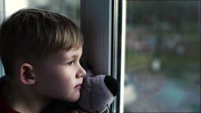 Niño solo triste de Little Boy con el oso cerca de mirar a través de ventana Little Boy almacen de video