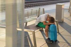Niño solo triste del muchacho que espera solamente con su equipaje foto de archivo