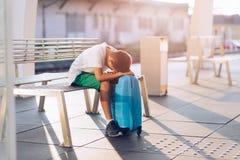 Niño solo triste del muchacho que espera solamente con su equipaje imagenes de archivo