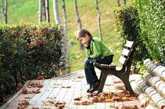 Niño solo triste en el parque Imagen de archivo libre de regalías