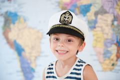 Niño sonriente caucásico adorable feliz en sombrero del capitán en fondo del mapa del mundo Imagen de archivo libre de regalías